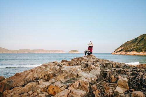 Woman sitting on rocky coast near waving sea