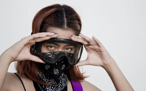 Woman in Black and White Floral Tank Top Wearing Black Mask