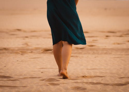 A Person Walking Alone on Sand