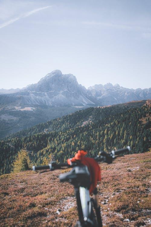 Человек в красной куртке сидит на черной скале и смотрит на горы