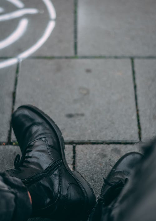 Close-Up Photo of a Person Wearing a Black Leather Shoes