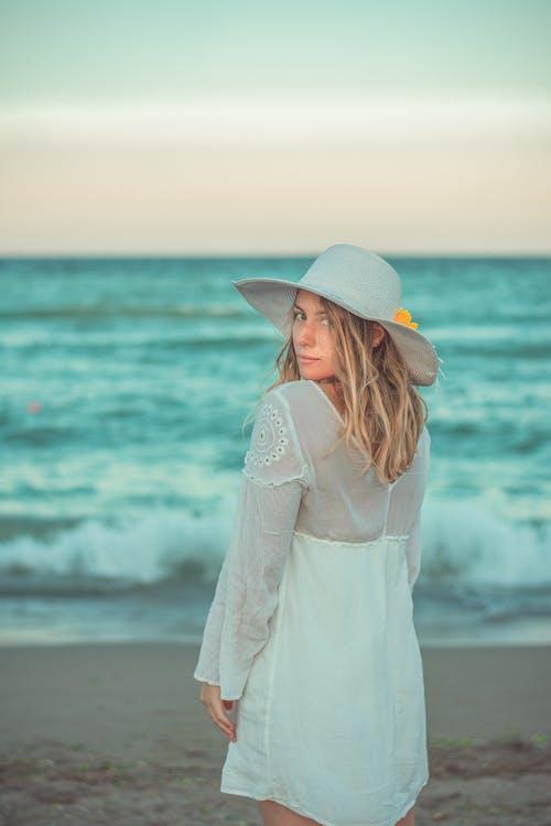 Woman in White Long Sleeve Dress Wearing White Sun Hat Standing on Seashore