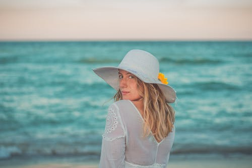 Woman in White Hat and White Long Sleeve Shirt Standing on Beach