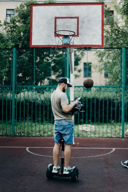 Man in Gray T-shirt and Blue Denim Shorts Holding Black Dslr Camera