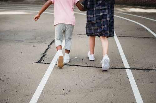 Kids in White Shoes Walking on Gray Concrete Flooring
