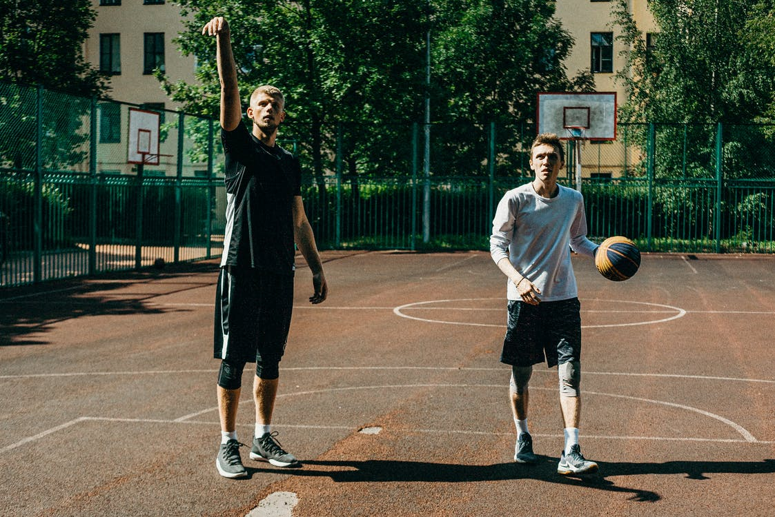 Man in White T-shirt and Black Shorts Holding Basketball