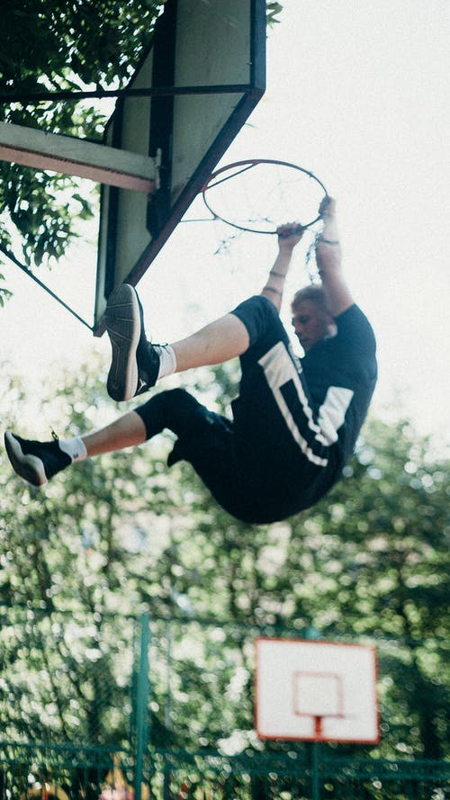 Man in Black and White Stripe Shirt and Black Shorts Jumping on Basketball Hoop