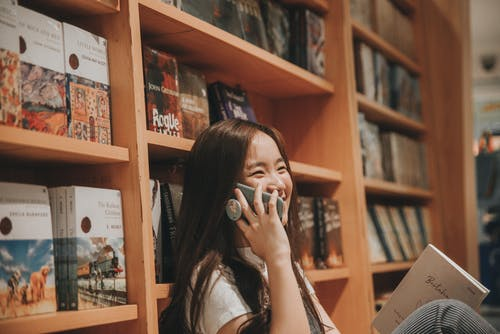 Happy Asian woman talking on smartphone in library