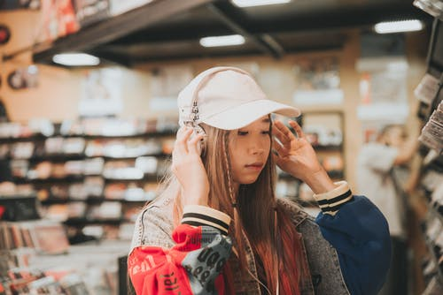 Trendy Asian student in headset and cap in book shop