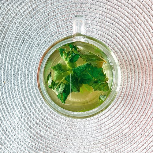 Top view of glass cup of aromatic herbal tea with leaves of mint placed on white textile surface in light room