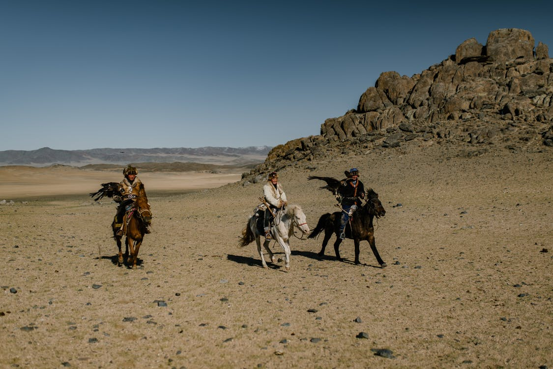 Ethnic people on horses near rocky formation