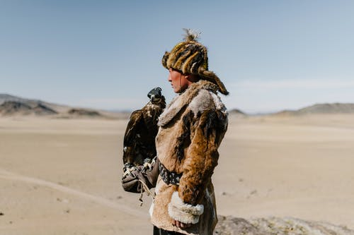 Mongolian man standing with eagle on hand in spacious valley