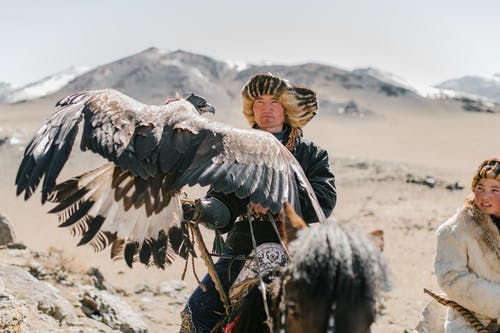 Serious Mongolian hunters with eagles riding horses in highlands