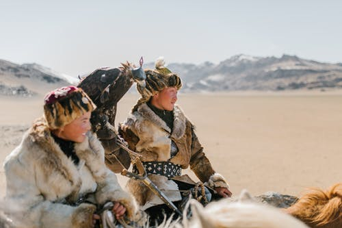 Positive young Mongolian people wearing authentic warm clothes and hats carrying golden eagle on hand and riding horses on vast mountainous valley while looking away contentedly
