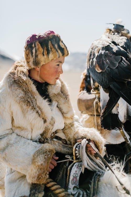 독수리 사냥 중 말을 타고 집중된 몽골 십 대 소년