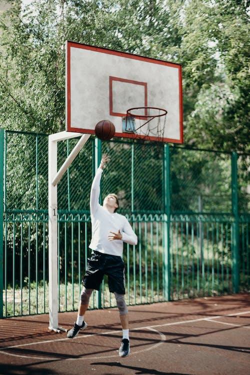 Man in White Shirt and Black Shorts Playing Basketball