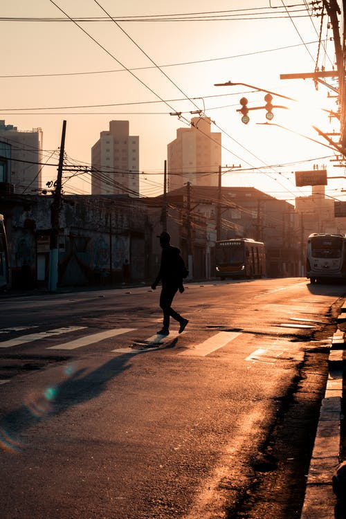Unrecognizable man on street at sunset