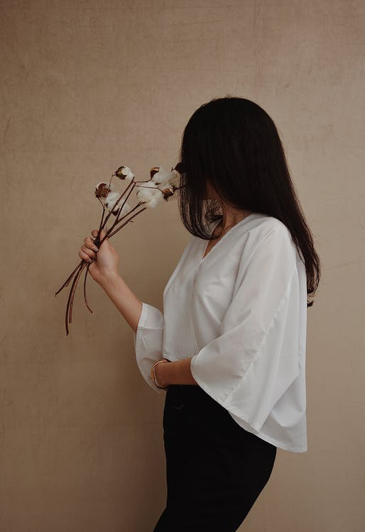 Faceless woman in trendy clothes with fluffy plants