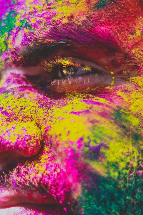 Closeup crop male face covered with multicolored powder paint and looking away in light
