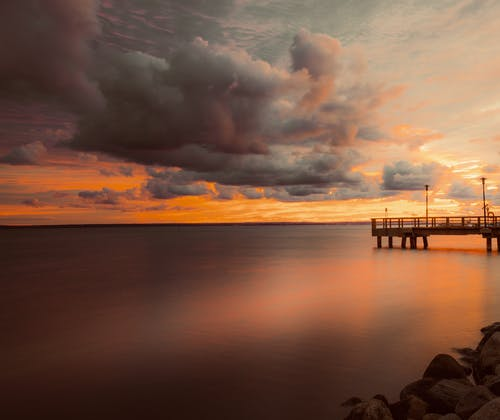 Magnificent landscape of wooden pier in calm ocean reflecting bright sunset sky with thick dramatic clouds