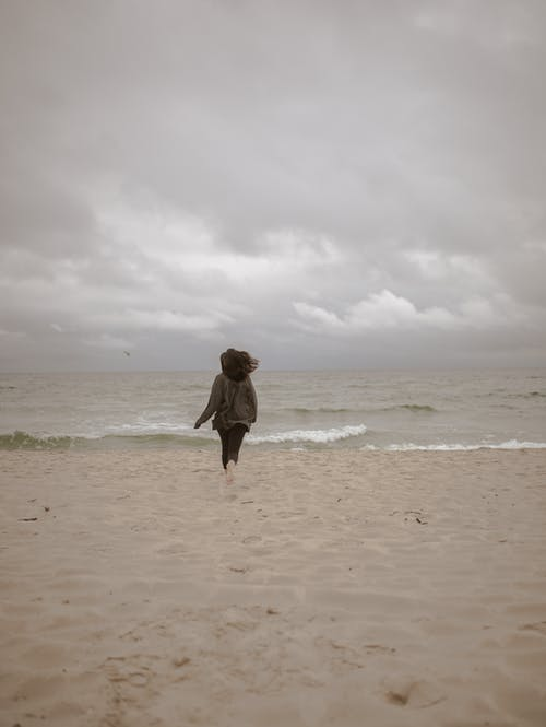 Unrecognizable woman running along sandy coast toward story sea on overcast day