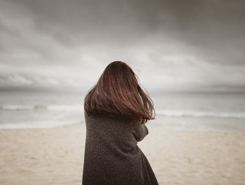 Unrecognizable tranquil young lady standing on sandy beach on cloudy day
