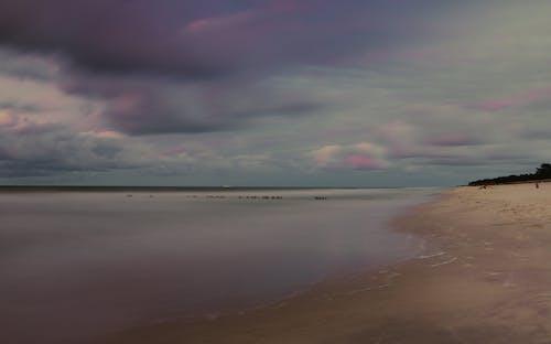 Sandy coastline of ocean against cloudy sundown sky