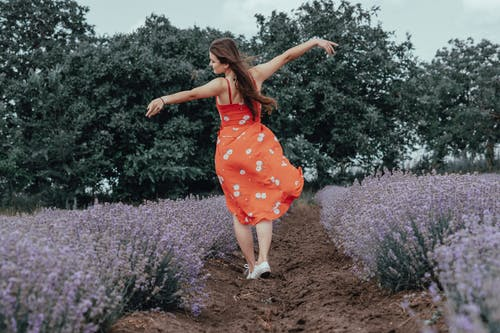 Woman in Red and White Floral Dress Standing on Purple Flower Field
