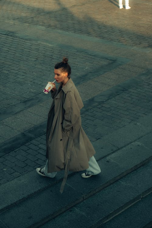 Woman in Brown Robe Standing on Gray Brick Floor