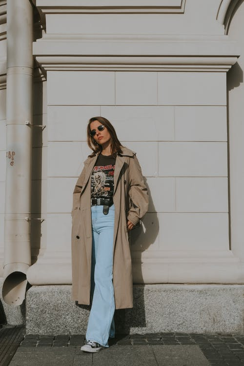 Woman in Brown Coat Standing Beside White Wall