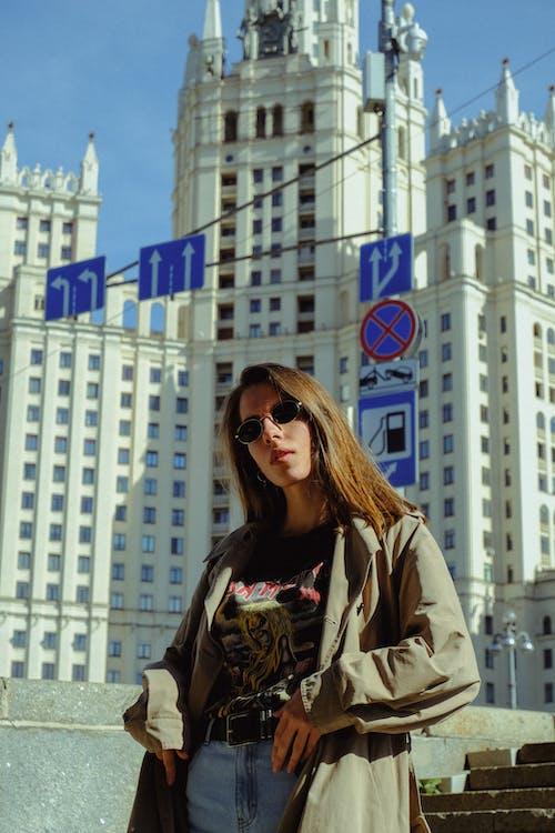 Woman in Beige Coat Wearing Sunglasses Standing Near High Rise Building