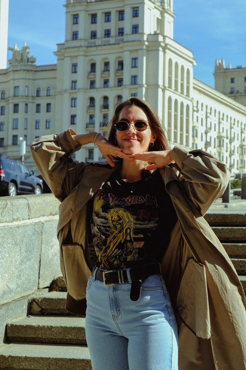 Woman in Brown Coat and Blue Denim Jeans Wearing Brown Sunglasses