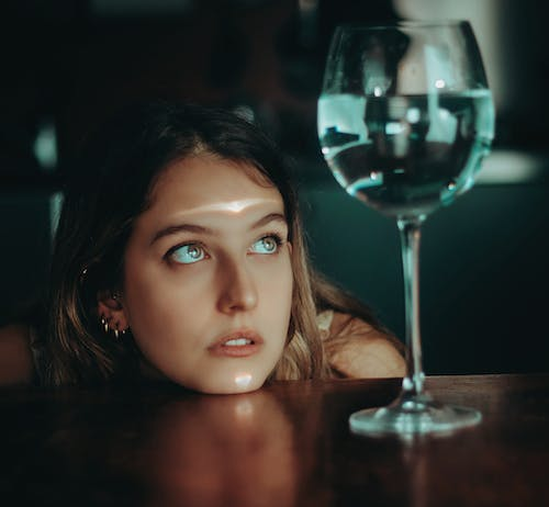 Thoughtful female sitting at table with glass of water
