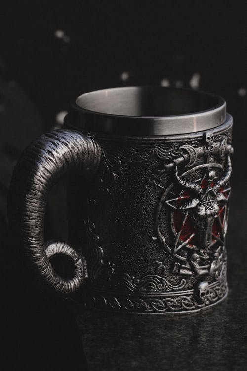 Gray metal mug with creepy design
