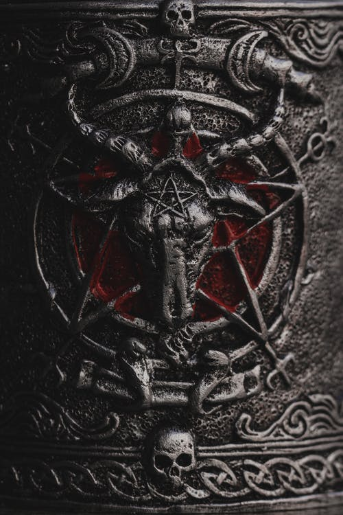Iron surface of object decorated with horned goat on devil pentagram and frightening skulls