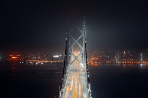 Modern suspension bridge with asphalt surface and lights of traffic leading to illuminated city at night