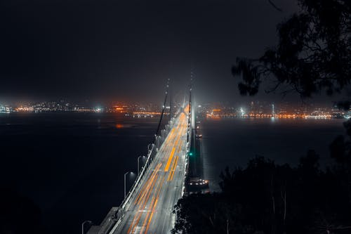 Illuminated modern bridge above dark river