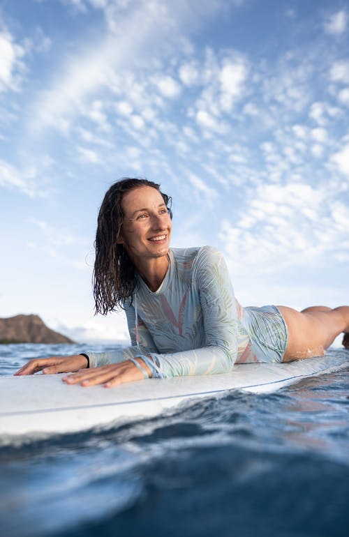 Happy young female traveler with wet hair lying on surfboard and looking away after training in wavy ocean on sunny day