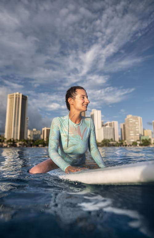Content young lady in wetsuit floating in sea sitting on surfboard while spending summer holidays in modern resort against blue sky