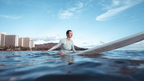 Low angle of relaxed young female surfer floating in rippling sea on paddleboard after training against blue sky