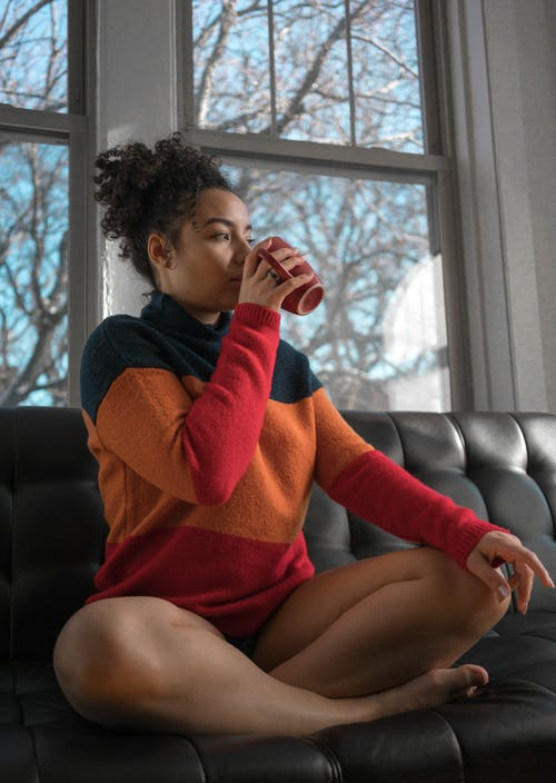 Full body of pensive barefooted young ethnic female in warm sweater sitting on sofa with crossed legs and drinking hot coffee