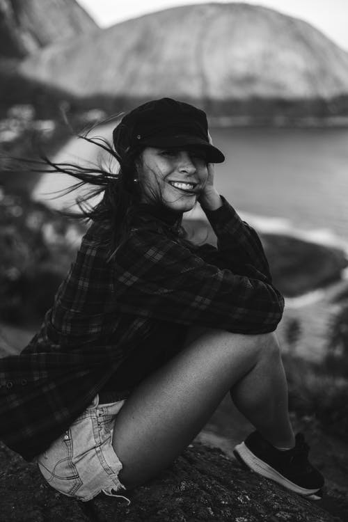 Woman in Plaid Shirt and Black Hat Sitting on Rock