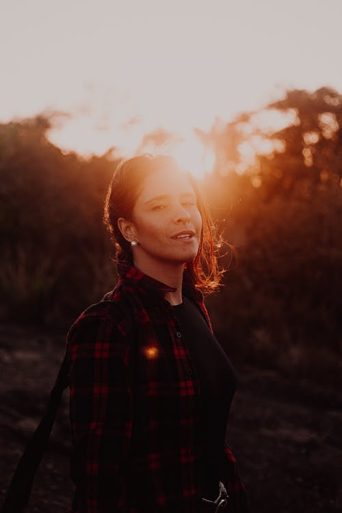 Woman in Black and Red Plaid Dress Shirt Standing Near Trees during Sunset