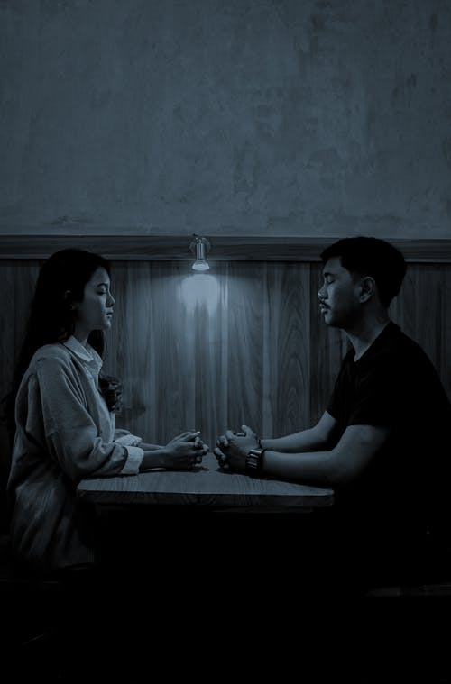 Asian couple at table in cafe at night