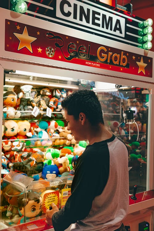 Man in Black Crew Neck Shirt Standing in Front of Plush Toys