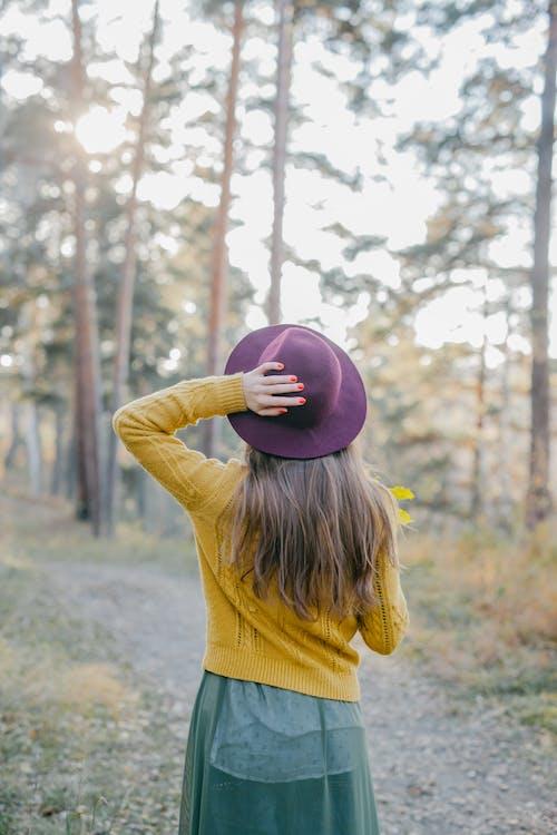 Frau Im Gelben Langarmhemd Und Im Lila Hut, Die Rosa Ball Halten
