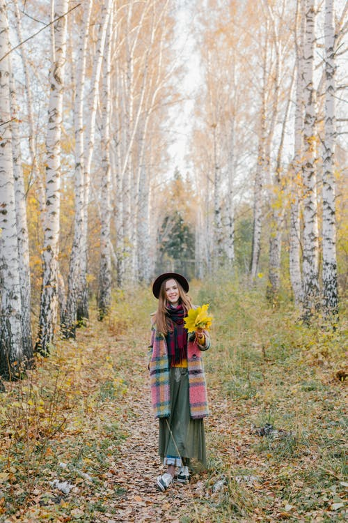 Woman in Green and Black Plaid Dress Shirt Standing in the Woods
