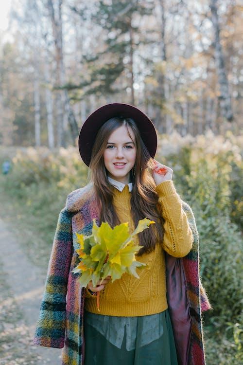 노란색 꽃을 들고 빨간색과 갈색 코트에 여자