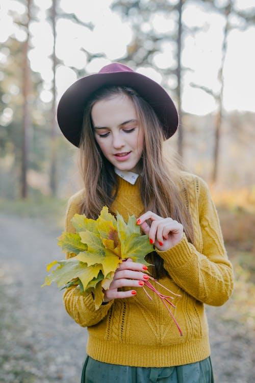 노란색 꽃을 들고 노란색 스웨터에 여자