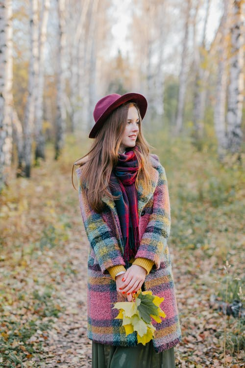 Woman in Green Red and Yellow Sweater Standing on Forest